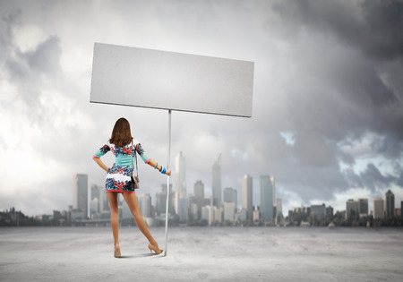 Rear view of young attractive woman with blank white banner photo