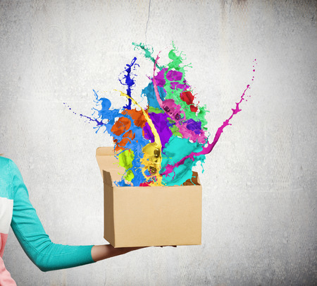 Close up of female hand holding carton box with colorful splashes photo