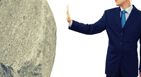 Businessman in suit huge holding stone in palm photo