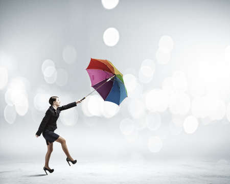 Young businesswoman walking with colorful umbrella against bokeh background photo