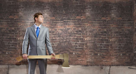Young determined businessman in suit holding big axe photo