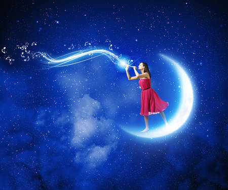 Young woman in red dress standing on moon and playing fife photo