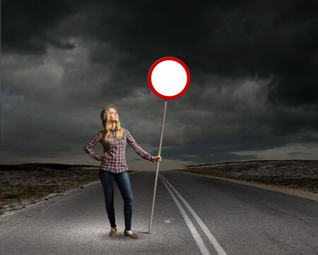 Young woman in casual holding road sign photo