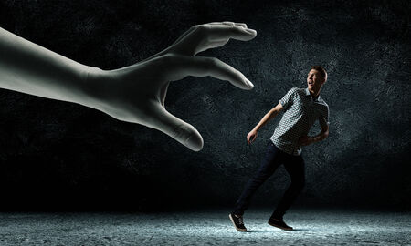 Funny image of young man trying to escape from huge hand photo