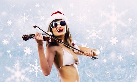 Young Santa girl in bikini playing violin photo