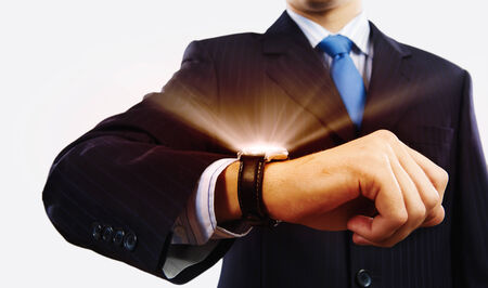 Businessman looking at wristwatch  Media technologies and innovations