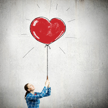 Young woman in casual holding heart shaped balloon