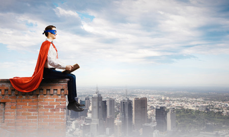 defend: Superman in cape and mask sitting on top of building and reading book Stock Photo