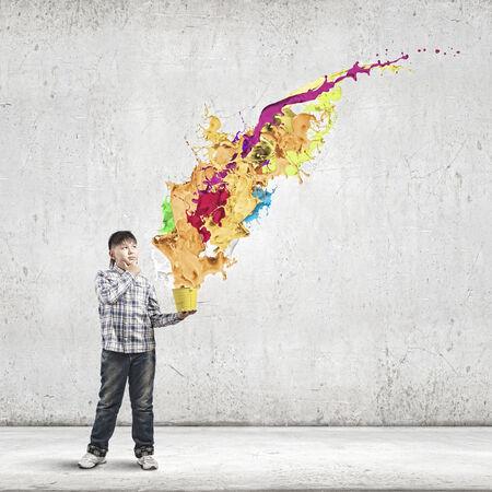 Cute boy splashing colorful paint from bucket photo