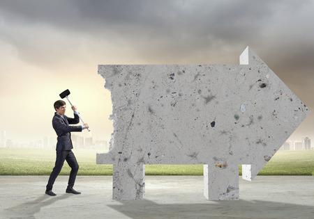 Young determined businessman breaking wall with hammer photo