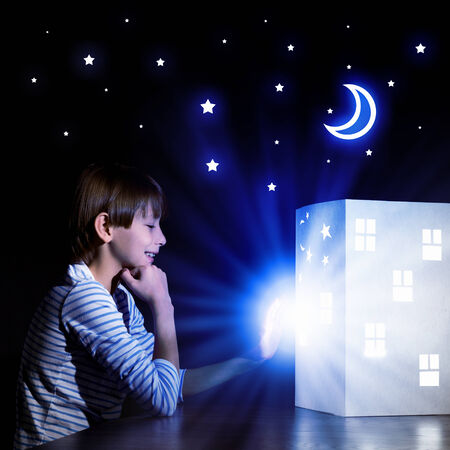 Cute little boy looking at model of house photo