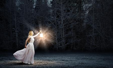 lampara magica: Mujer joven en blanco vestido largo caminar en la noche de madera