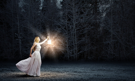 find: Young woman in white long dress walking in night wood