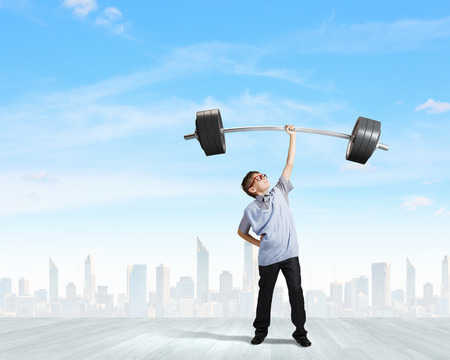 Cute boy of school age lifting barbell above head
