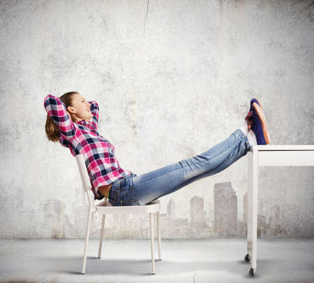 Young woman in casual with legs on table photo