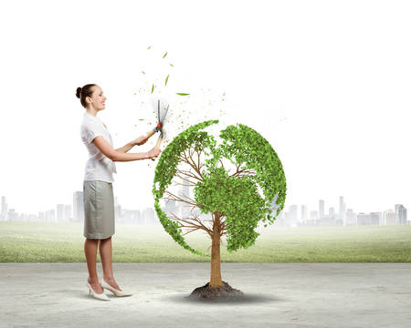 Young businesswoman cutting tree with scissors in shape of Earth planet photo