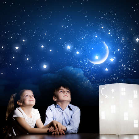 Cute little boy and girl looking at model of house photo