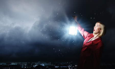 Young scared woman in red cloak with lantern photo