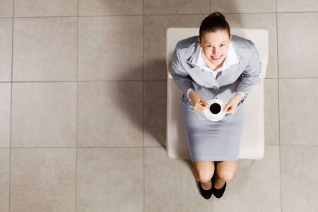 Top view of busineswoman sitting on chair with cup of coffee photo
