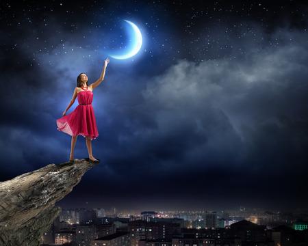 Jonge vrouw in rode jurk staande op de rand van de rots Stockfoto