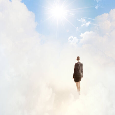 Back view of businesswoman standing on cloud high in sky photo