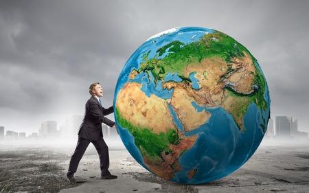 Businessman pushing big Earth planet   photo