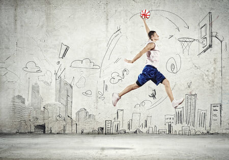 Young man throwing ball into basket in jump photo