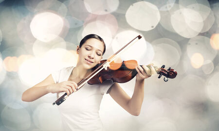 woman violin: Young attractive woman playing violin with bokeh lights at background