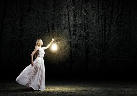 faroles: Mujer joven en blanco vestido largo caminar en la noche de madera