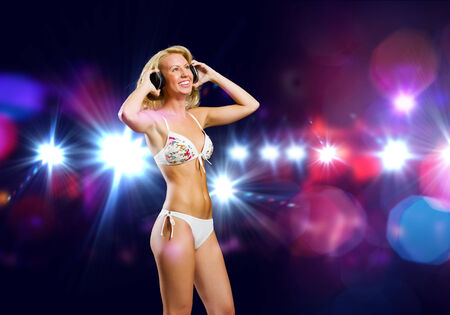 Attractive girl in headphones having fun at disco party photo