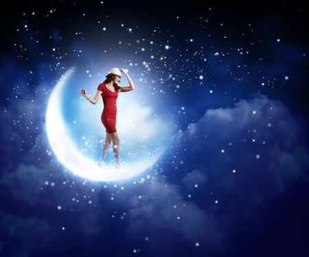 Young woman in red dress walking on moon photo