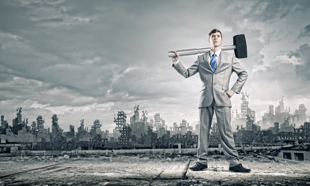 Young businessman with hammer and ruins at background