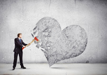 Young businessman breaking stone heart with axe photo