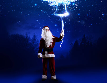 Santa Clause in red costume against blue background photo
