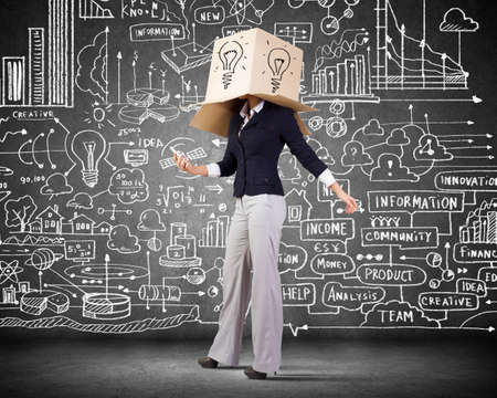 Businesswoman using mobile phone wearing carton box on head photo
