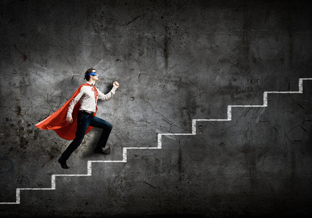 Young confident superman in mask and cape walking on ladder photo
