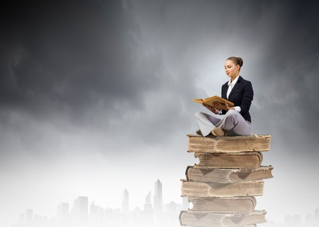 Young attractive woman sitting on pile of books and reading photo