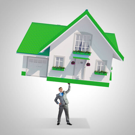 Young businessman lifting huge model of house above head photo