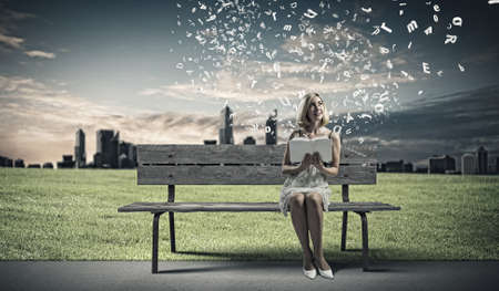 Young pretty woman sitting on bench and reading book photo
