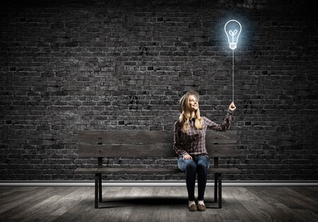 Young woman in casual holding bulb balloon photo