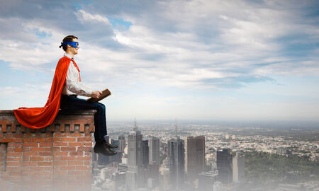Superman in cape and mask sitting on top of building and reading book Stock Photo