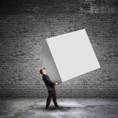 Young businessman carrying white blank cube  Place for text photo