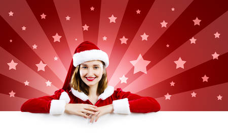Young attractive woman in santa suit holding blank banner  Place for text photo