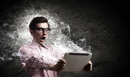 젊은 남자는 태블릿 PC에 충격을 찾고 스톡 콘텐츠
