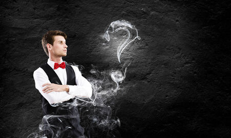 Young handsome businessman in fumes smoking pipe photo
