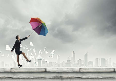 Young businesswoman walking on roof with colorful umbrella photo