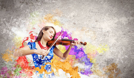 Young attractive woman in blue dress playing violin photo