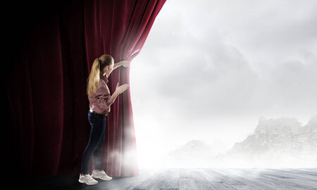 behind scenes: Young woman in casual opening red curtain and looking at clear sky