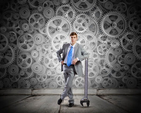 Young determined businessman leaning on wrench and cogwheels at background photo