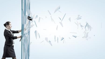 Jonge vastberaden zakenvrouw brekend glas met hamer